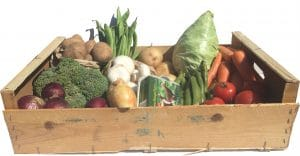 wooden box containing local seasonal vegetables.