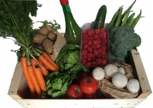 Wooden Box containing fresh Vegetables, Salads, Fruits and Apple Juice.
