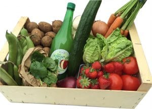 A wooden Box containing a selection of local veg, fruit and salad.