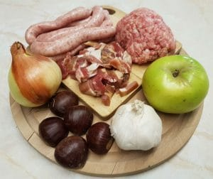 Photo of the trimmings box which includes sausage meat, chipolata sausages, bacon lardons, onion, chestnuts, garlic and bramley apple.